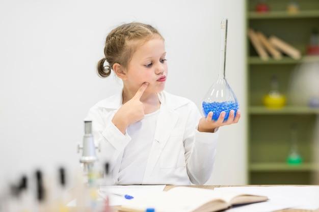 Mädchen, das wissenschaftsrohr betrachtet