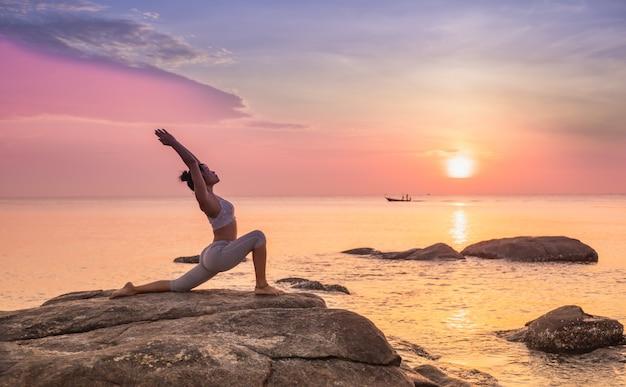 Mädchen, das yoga auf einem felsen praktiziert