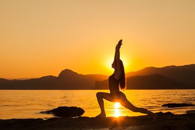 Mädchen, das yoga durch den ozean tut.