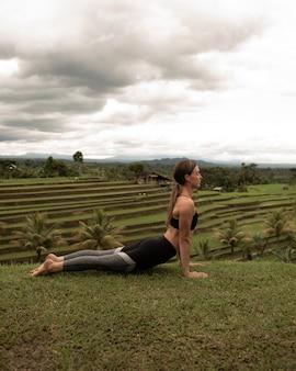 Mädchen, das yoga in einem offenen land tut