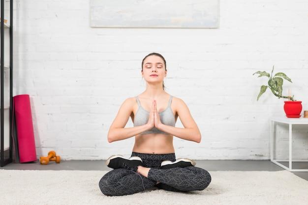 Mädchen, das yoga in ihrem haus bildet