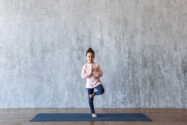 Mädchen, das yoga praktiziert, das auf einer matte in einer baumpose steht, im fitnessstudio trainiert, gegen die szene einer dachbodenwand mit freiem platz