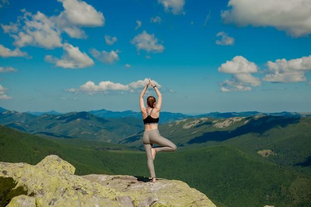 Mädchen, das yoga-übungslotus auf der spitze des berges tut.
