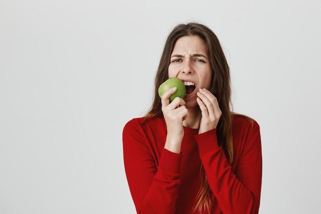 Mädchen, das zahnschmerzen und grimassenbildung vom schmerz als beißenden grünen apfel fühlt