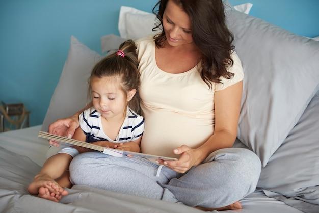 Mädchen, das zeit auf dem lesen mit mama verbringt