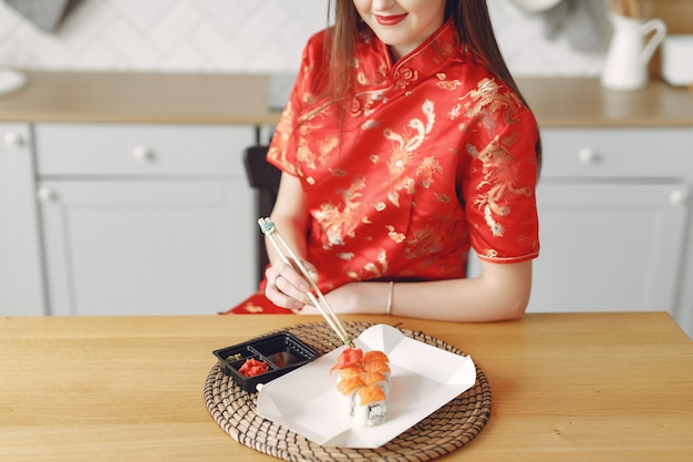 Mädchen, das zu hause am tisch mit einem sushi sitzt