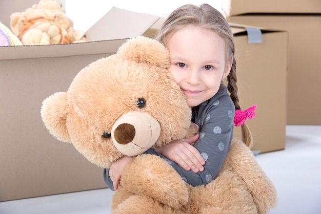 Mädchen, das zu hause einen großen bären und ein lächeln umarmt.