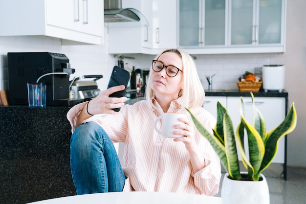 Mädchen, das zu hause küche sitzt und videoanruf hält.