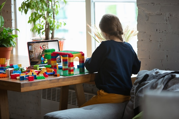 Mädchen, das zu hause mit dem konstruktor spielt und das online-tutorial des lehrers auf dem laptop ansieht.