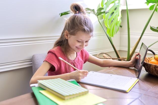 Mädchen, das zu hause mit digitaler tablette studiert. fernunterricht, online-unterricht, videokonferenz, schulunterricht in elektronischer form. moderne schule, technologie, bildung, kinderkonzept.