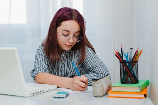 Mädchen, das zu hause mit laptop arbeitet und hausaufgaben macht