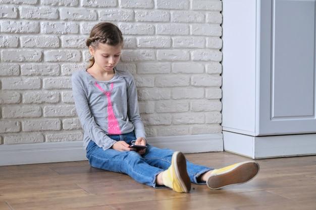 Mädchen, das zu hause mit smartphone sitzt. gadget-missbrauch durch kleine kinder