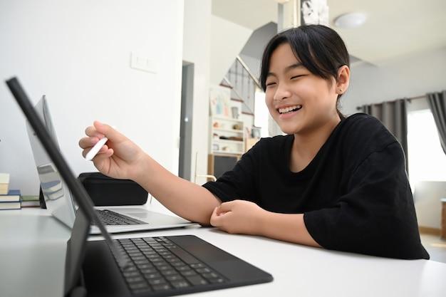Mädchen, das zu hause online-unterricht mit digitaler tablette studiert. online-bildungskonzept. Premium Fotos