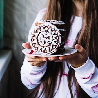 Mädchen, das zuckerglasurplätzchen auf platte hält