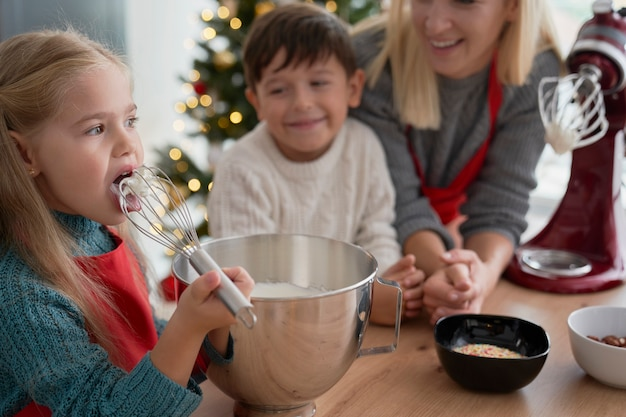 Mädchen, das zuckerpaste während des backens mit familie schmeckt