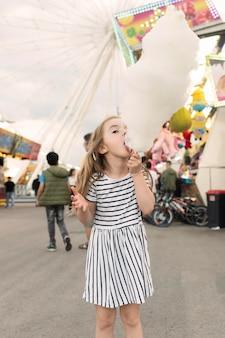 Mädchen, das zuckerwatte genießt