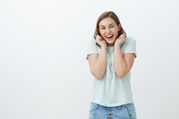 Mädchen, das zum ersten mal konzert besucht. charmante faszinierte und glückliche junge frau im trendigen t-shirt, die vor freude und aufregung schreit und hände in der nähe des gesichts hält, um auf großartige neuigkeiten zu reagieren