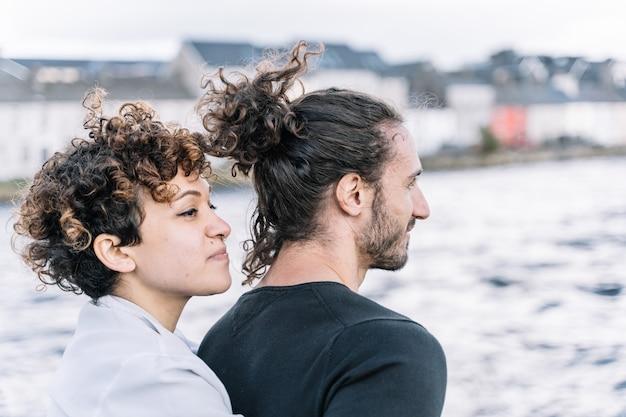 Mädchen, das zurück ihren partner mit dem meer unscharf umarmt