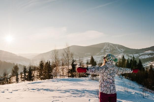 Mädchen, das zurücksteht und die schneebedeckten winterberge betrachtet. genießt die landschaft. spazieren sie in der natur. frostsaison. kaltes wetter, schnee auf hügeln. wandern. bergsteiger an der spitze an einem sonnigen wintertag.
