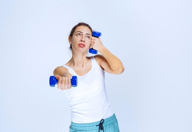 Mädchen, das zwei ein kilogramm blaue hanteln hält und mit ihnen trainiert.