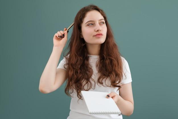 Mädchen denkt, was sie in ihr notizbuch schreiben soll