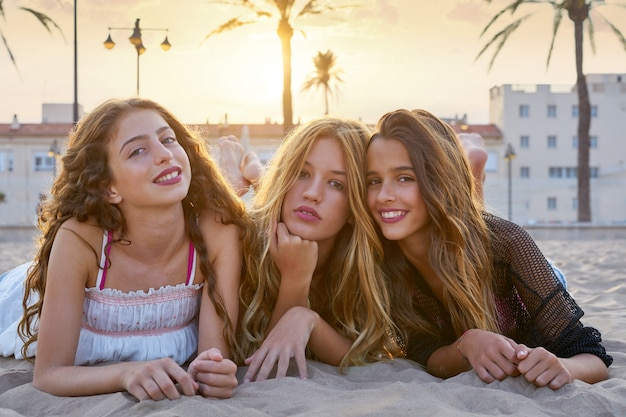 Mädchen der besten freunde am sonnenuntergangstrandsand