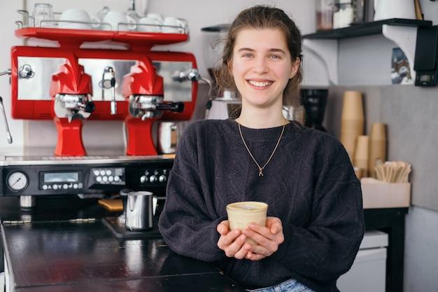 Mädchen der generation z, das im café arbeitet und kaffee kocht