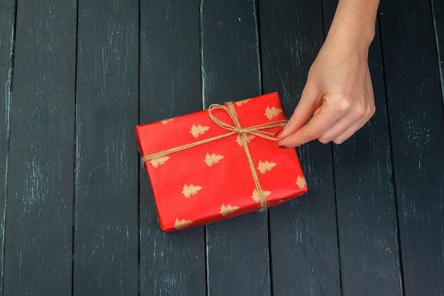 Mädchen der geschenkbox in der hand auf hölzerner tabelle