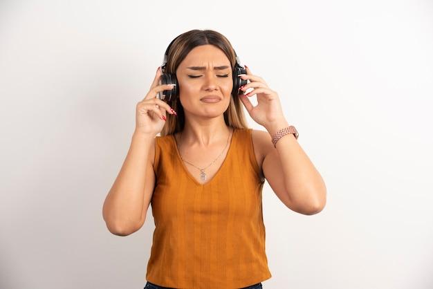 Mädchen der jungen frau in der freizeitkleidung, die mit kopfhörern aufwirft.