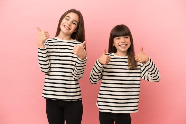 Mädchen der kleinen schwestern einzeln auf rosa hintergrund, die mit beiden händen eine geste mit dem daumen nach oben geben und lächeln