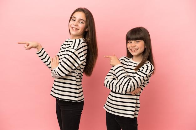 Mädchen der kleinen schwestern einzeln auf rosafarbenem hintergrund, die mit dem finger zur seite in seitlicher position zeigen