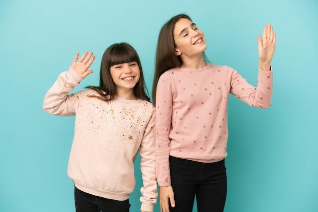Mädchen der kleinen schwestern lokalisiert auf blauem hintergrund, die mit der hand mit glücklichem ausdruck grüßen