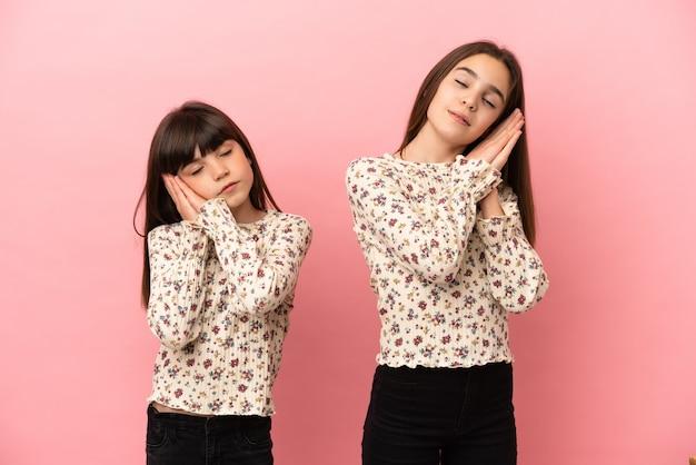Mädchen der kleinen schwestern lokalisiert auf rosa hintergrund, der schlafgeste in liebenswürdigem ausdruck macht