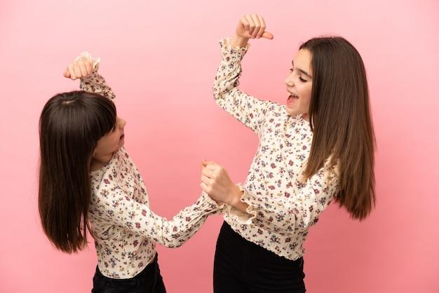 Mädchen der kleinen schwestern lokalisiert auf rosa hintergrund, die einen sieg in der siegerposition feiern