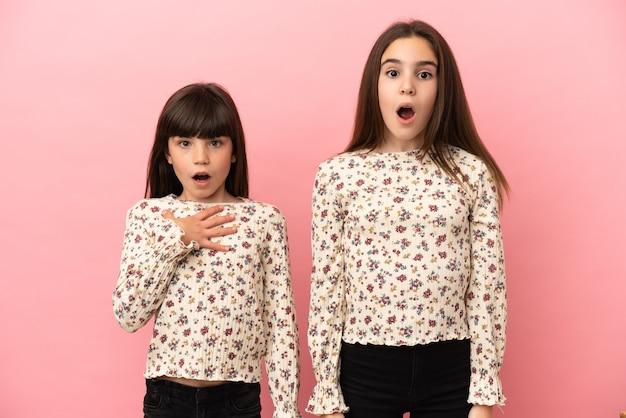 Mädchen der kleinen schwestern lokalisiert auf rosa hintergrund mit überraschung und schockiertem gesichtsausdruck