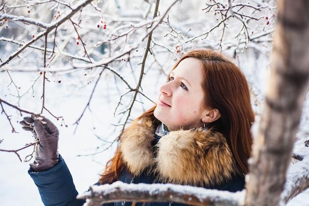 Mädchen des europäischen aussehens auf einem spaziergang im winterwald, park, winter und schnee, gesundheit, winterkleidung, jacke