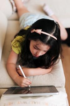 Mädchen des hohen winkels, das auf das sofa mit ihrer tablette legt