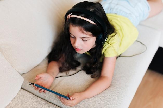 Mädchen des hohen winkels, das auf der couch mit telefon sitzt