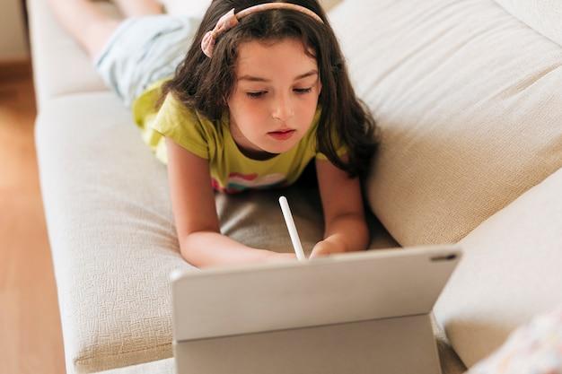 Mädchen des hohen winkels mit dem stift, der ihre tablette betrachtet