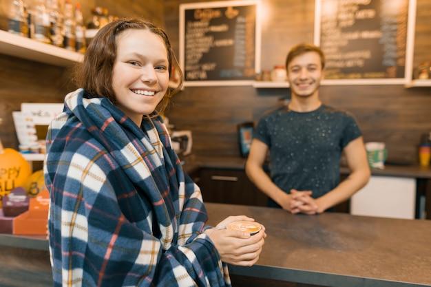 Mädchen des jungen jugendlich, das einen kaffee mit barista kauft