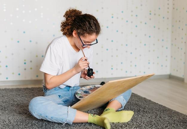 Mädchen des lockigen haarmädchens in den gläsern im weißen t-shirt, das auf bodenmalerei auf hölzernem schreibtisch am haus sitzt