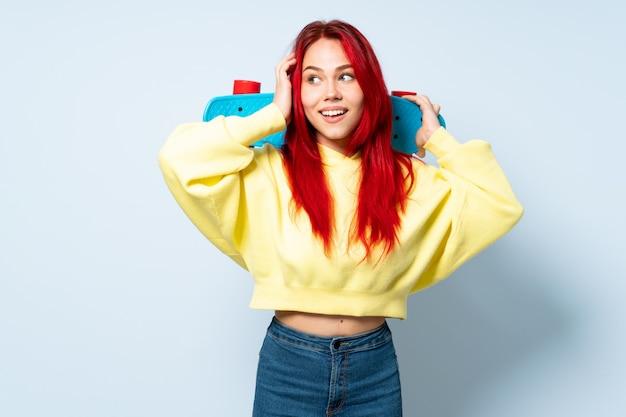 Mädchen des roten haares des teenagers lokalisiert auf blauer wand mit einem skate und nach oben schauend