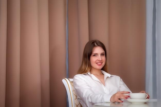 Mädchen des slawischen aussehens mit telefon und weißer tasse sitzt am tisch