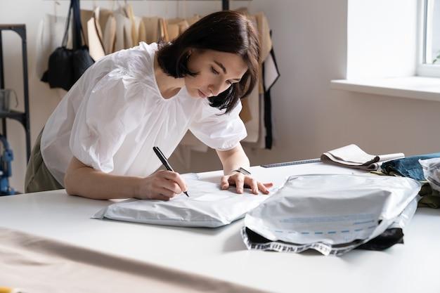 Mädchen-designer bereiten kleidung für die lieferung an den kunden vor oder verkaufen schneider-geschäftsinhaber-tap-kleidung