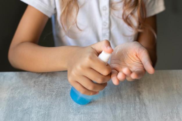 Mädchen desinfiziert ihre hände beim sitzen an ihrem schreibtisch