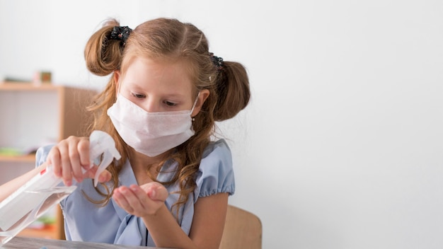 Mädchen desinfiziert in der klasse mit kopienraum