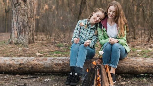 Mädchen, die am lagerfeuer wärmen