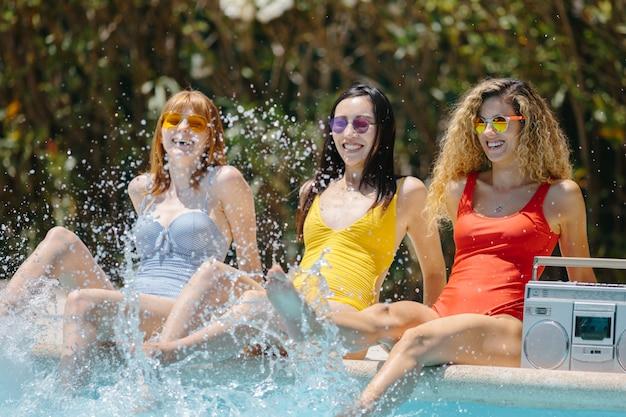 Mädchen, die am rand eines pools sitzen und mit ihren füßen wasser spritzen