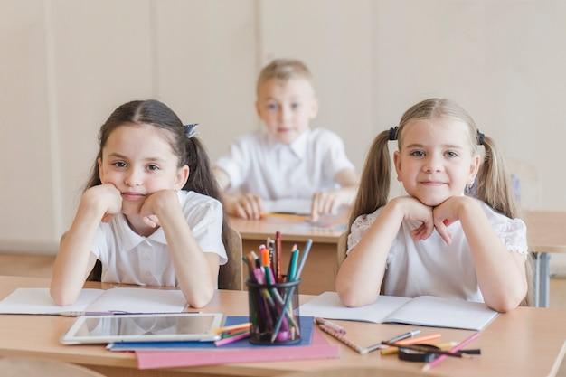 Mädchen, die am schreibtisch im klassenzimmer sitzen