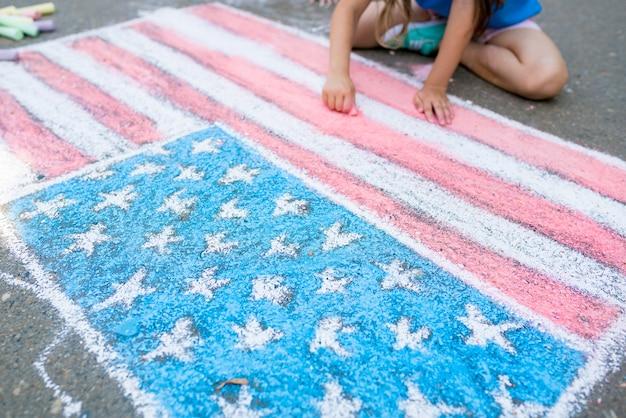 Mädchen, die amerikanische flagge mit farbigen kreiden auf dem bürgersteig zeichnen